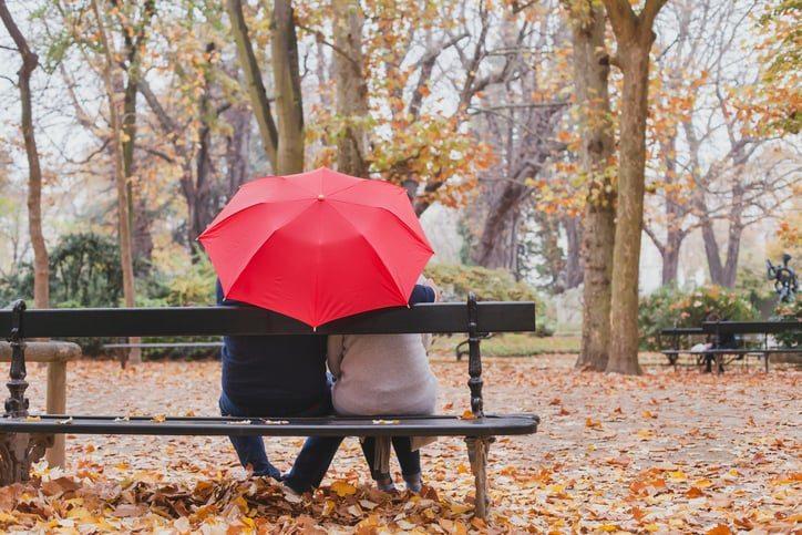 Deux seniors amoureux sur un banc avec un parapluie.